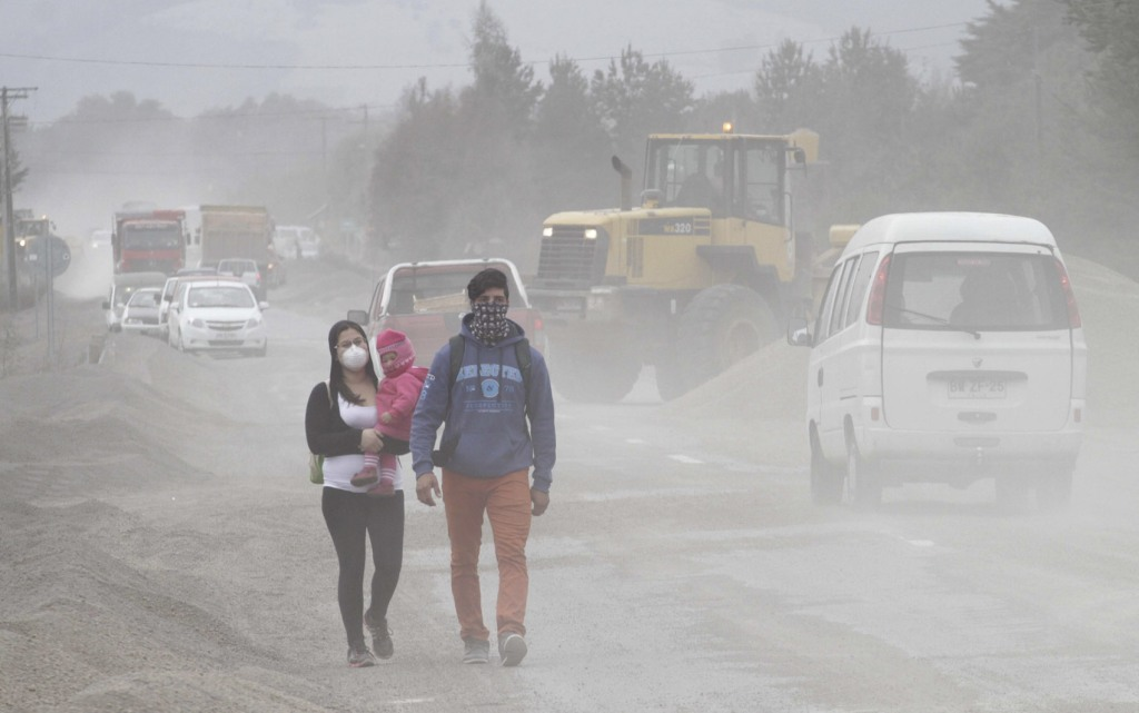Residents wearing surgical masks to protect themselves against ash from Calbuco volcano, walk in a street in Ensenada