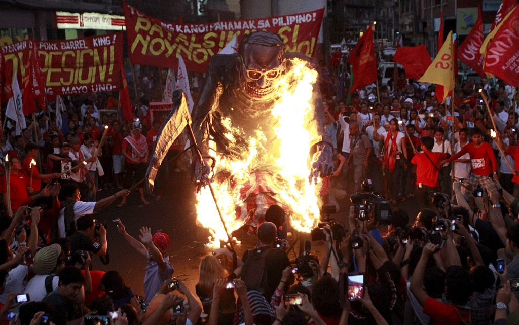 Workers burned an effigy of Philippine President Benigno Aquino during a May Day protest outside the presidential palace in Manila