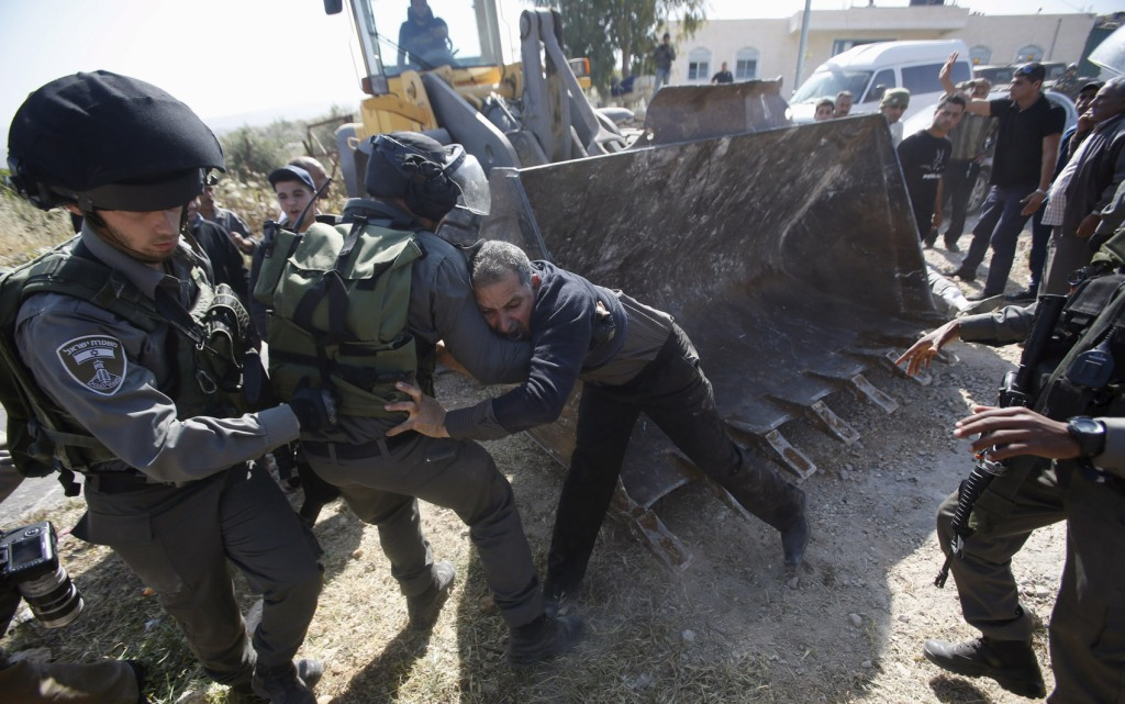 Israeli border policemen scuffle with a Palestinian man as Israeli forces bulldoze a farmland in Soba village near the West Bank city of Hebron