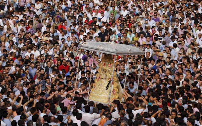Pilgrims crowd around the Virgin of El Rocio during a procession around the shrine of El Rocio in Almonte, southern Spain