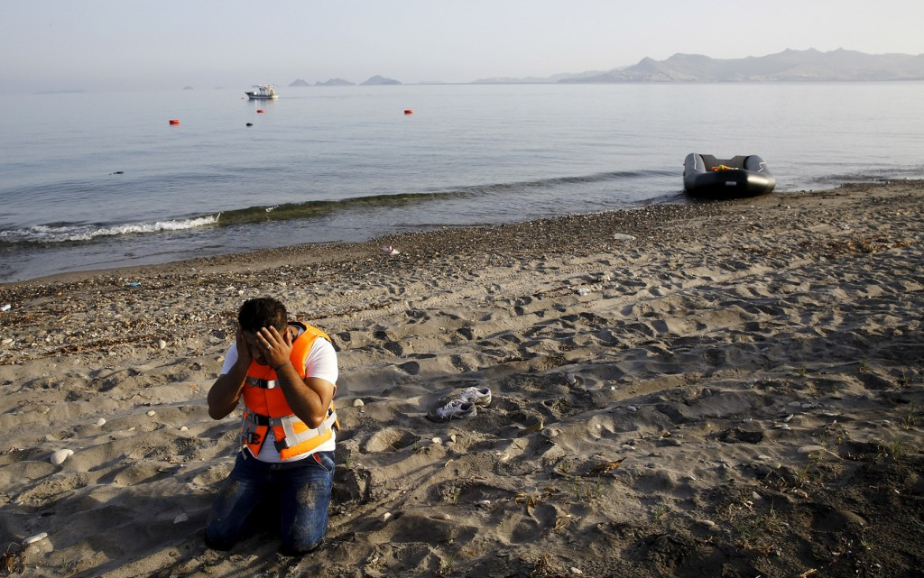 A Syrian refugee prays after arriving on Kos on a dinghy boat, after crossing part of the Aegean Sea from Turkey to Greece