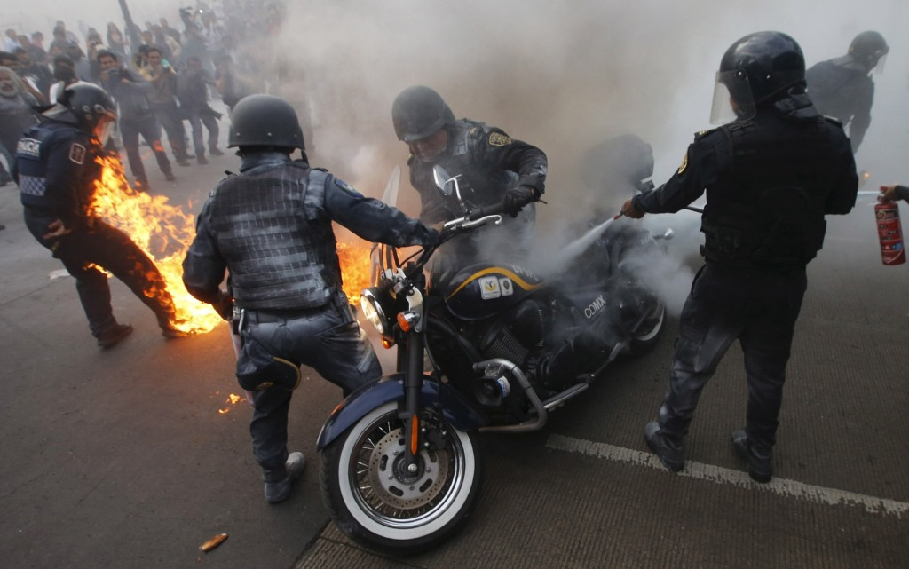 Policemen extinguish a fire on a motorcycle as one of their colleagues catches fire after being hit by a Molotov cocktail during a protest to mark the eight-month anniversary of the Ayotzinapa students' disappearance in Mexico City