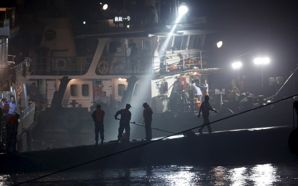 Rescue workers are seen atop the sunken ship in the Jianli section of Yangtze River