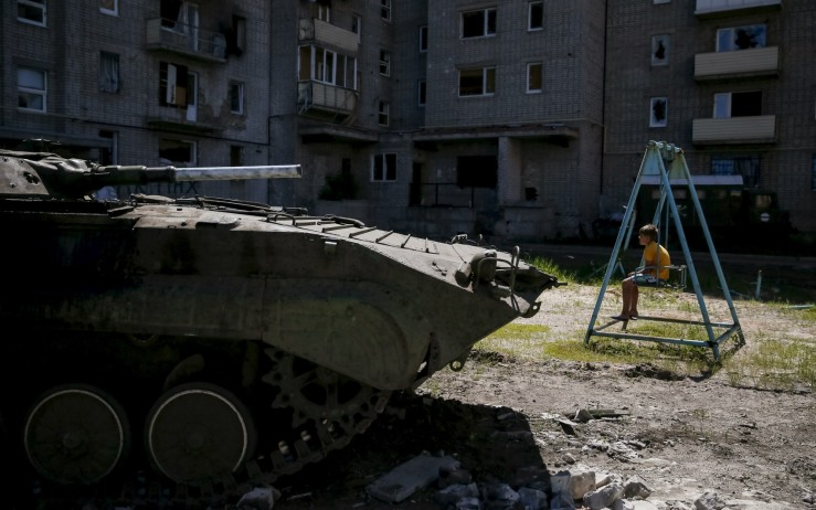 Boy sits on a swing near his building, which was damaged during fighting between the Ukrainian army and pro-Russian separatists, as an APC of the Ukrainian armed forces is seen nearby in Avdeyevka near Donetsk