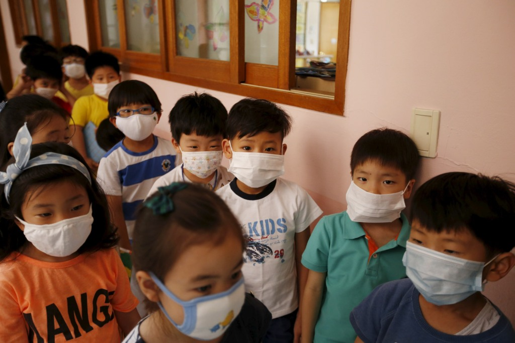 Elementary school students wearing masks to prevent contracting Middle East Respiratory Syndrome (MERS) wait in a line outside their classroom at an elementary school in Seoul