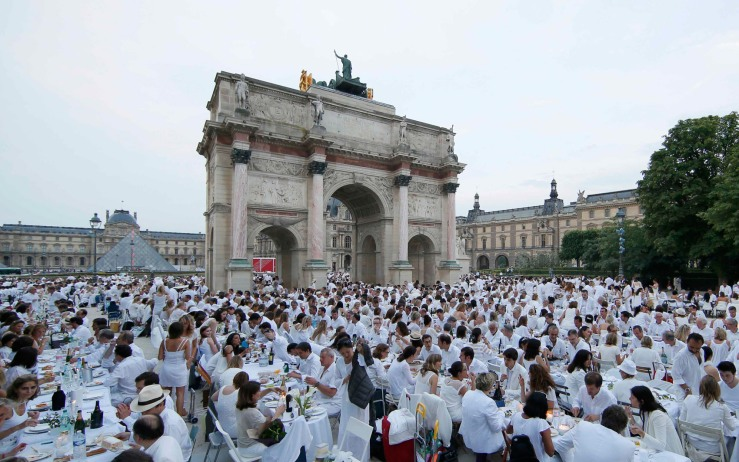 Diners gather at their tables in the Tuileries Gardens near the Louvre Museum during the Diner en Blanc (Dinner in White) in Paris