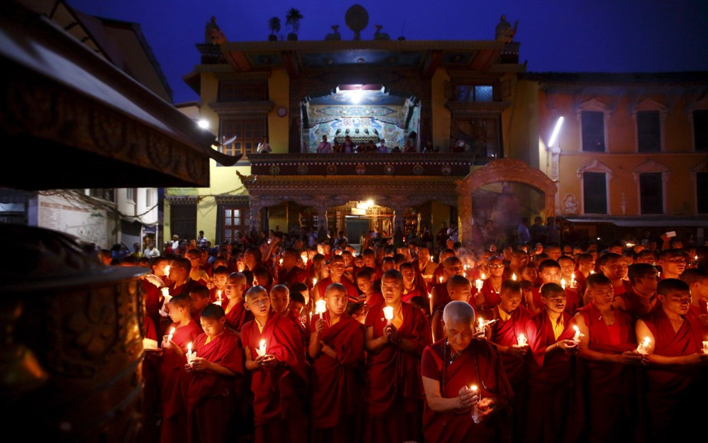 Buddhist monks holding candles offer prayers for the victims of earthquakes in Kathmandu