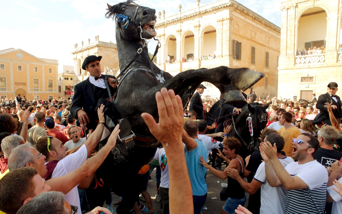 Rider rears up on his horse while surrounded by a cheering crowd during the traditional Fiesta of San Joan (Saint John) in downtown Ciutadella on Balearic Island of Menorca