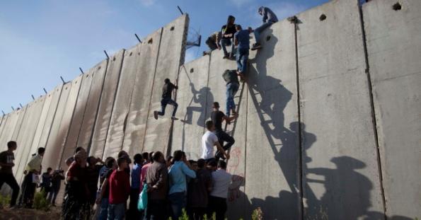 3jul2015---palestinos-usam-uma-escada-para-escalar-muro-erguido-por-israel-que-os-separa-da-regiao-onde-fica-a-mesquita-al-aqsa-em-jerusalem-1435912578520_956x500