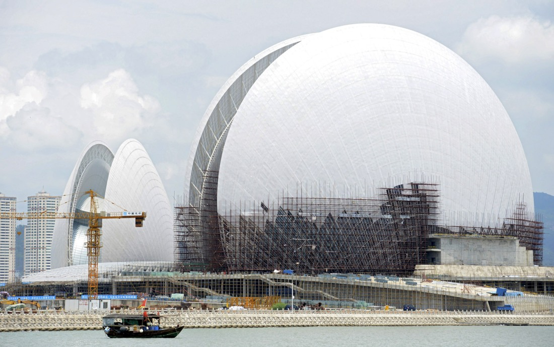 A boat travels past the Zhuhai Opera House under construction off the coast of the Yeli Island, in Zhuhai