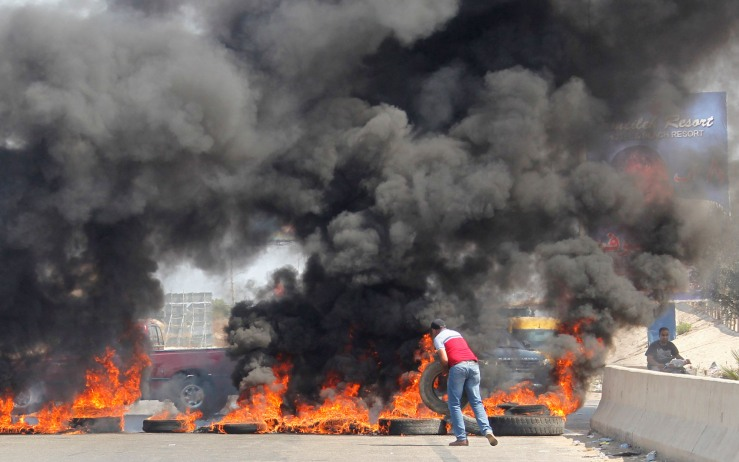 Protesters set tires on fire and block a highway in Jiyyeh, south of Beirut as they protest against a rubbish collection problem in the capital Beirut, Lebanon